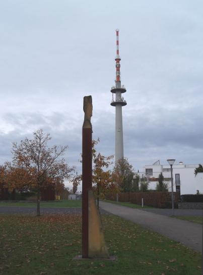 """Skulptur """"Wächter der Bäume"""" des französischen Bildhauers Guy Charlier, im Hintergrund der Fernsehturm"""